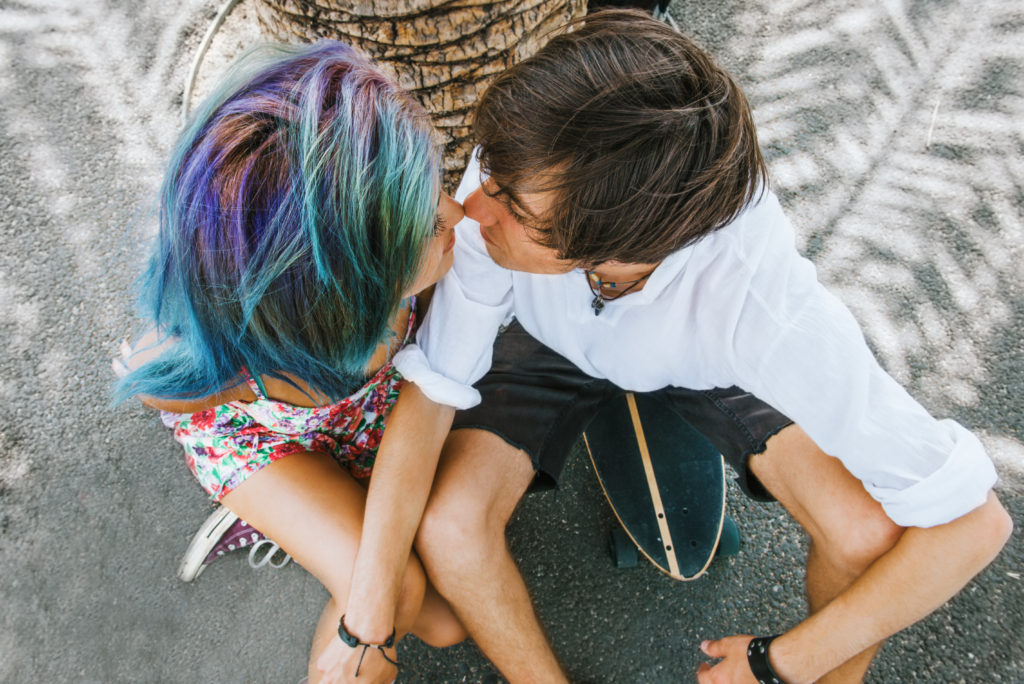 Skateboard couple is kissing under the palm tree